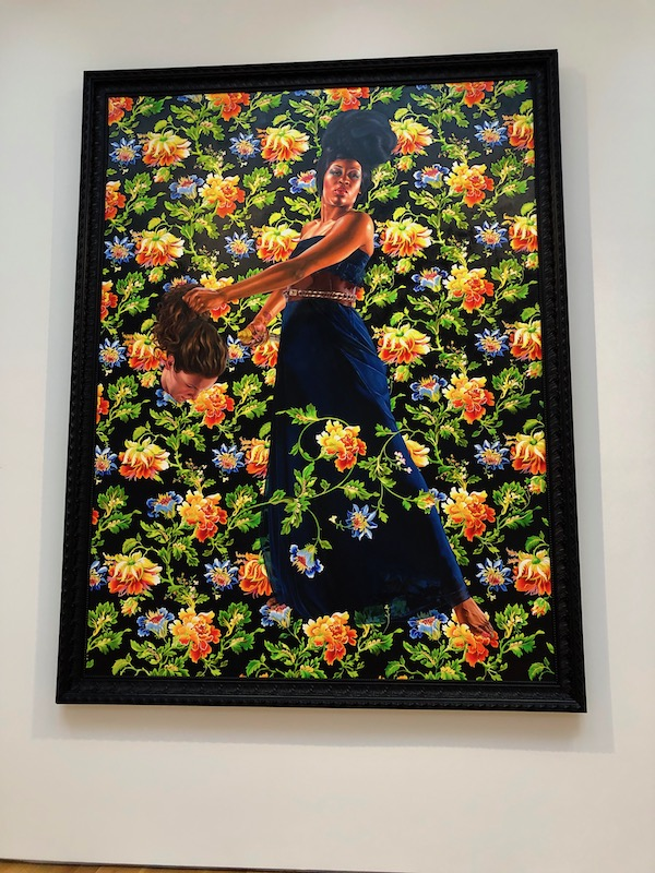 A painting of and African woman amongst yellow and orange flowers