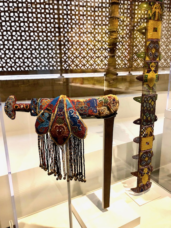 A glass enclosure with African art on display