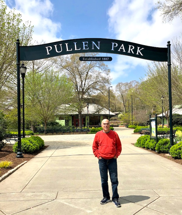 A man in a red sweater standing under an arch that reads Pullen Park with trees behind him.