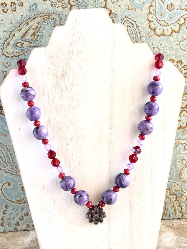 Charoite, Ruby Quartz and Swarovski Crystal Necklace on a white washed wood display.