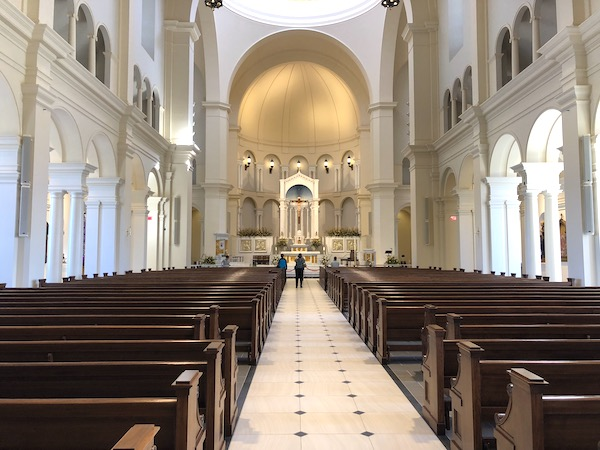 A view of the alter ofHoly Name of Jesus Cathedral in Raleigh NC with pews in the foreground.