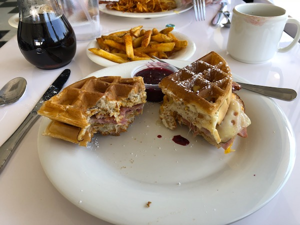 A white plate with a waffle grilled ham and Swiss with jam. Behind it are French fries, Maple syrup and a white coffee mug.