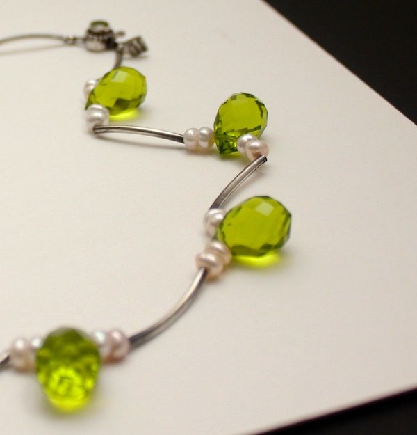 Partial view of a necklace of teardrop shaped faceted peridots, freshwater pears and sterling silver curved tubes on a white board.