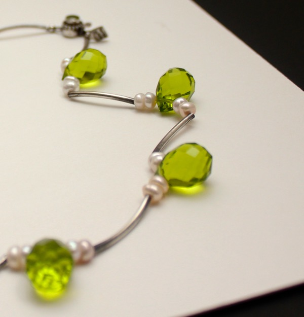 Partial view of a necklace of teardrop shaped faceted peridot, sterling silver and freshwater pearls with curved sterling silver tubes on a white board.