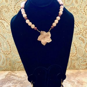 Rose quartz and chocolate pearl necklace with carved rose quartz flower at center.