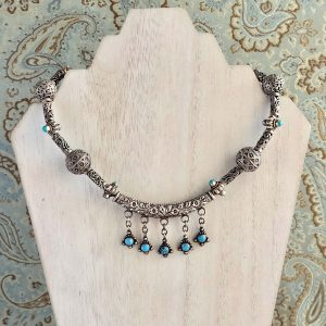 Oxidized Sterling Silver and Turquoise Necklace on a white washed display stand.