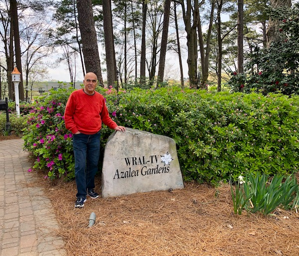 A man in a red sweater stand by a small rock monument that says WRAL-TV Azalea Gardens.