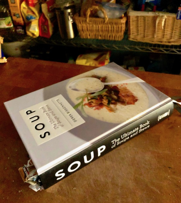 Side view of a cookbook called Soup by Derek Bissonnette sitting on a butcher block.