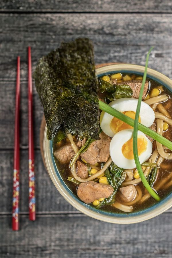 A rustic pale green soup bowl filled with chicken, broth, ramen, two hard boiled egg halves and nori. A pair of red chopsticks is to the left of the bowl.