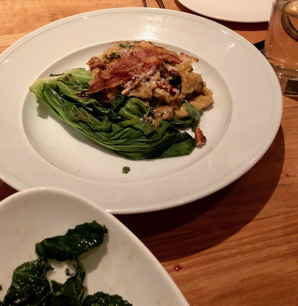 A large white plate topped with pasta, guanciale, caramelized onion and charred bok choy.