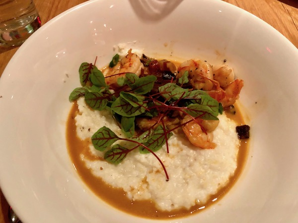 A large white bowl filled with shrimp and grits.