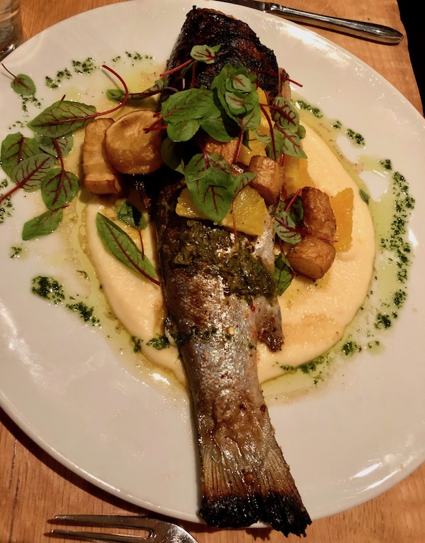 A large white plate topped with whole trout, vegetable puree, charred citrus and fried parsnips.