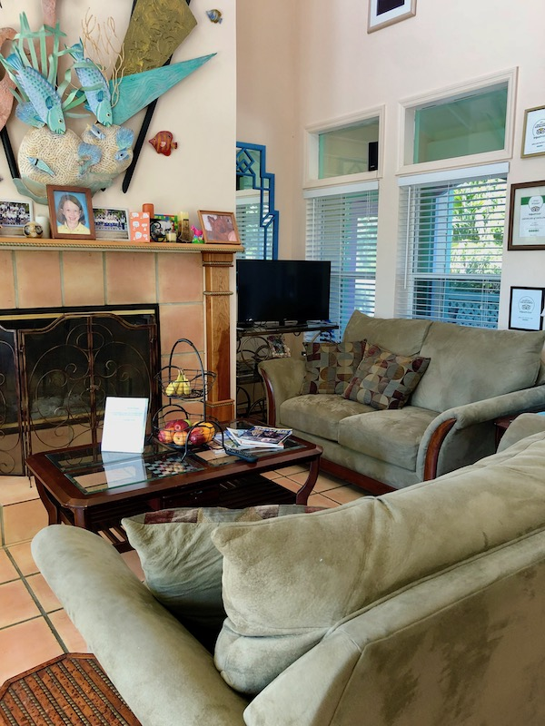 A living room with two sofas, lots of windows and a large fireplace at the Mellon Patch Inn on N. Hutchinson Island Florida.
