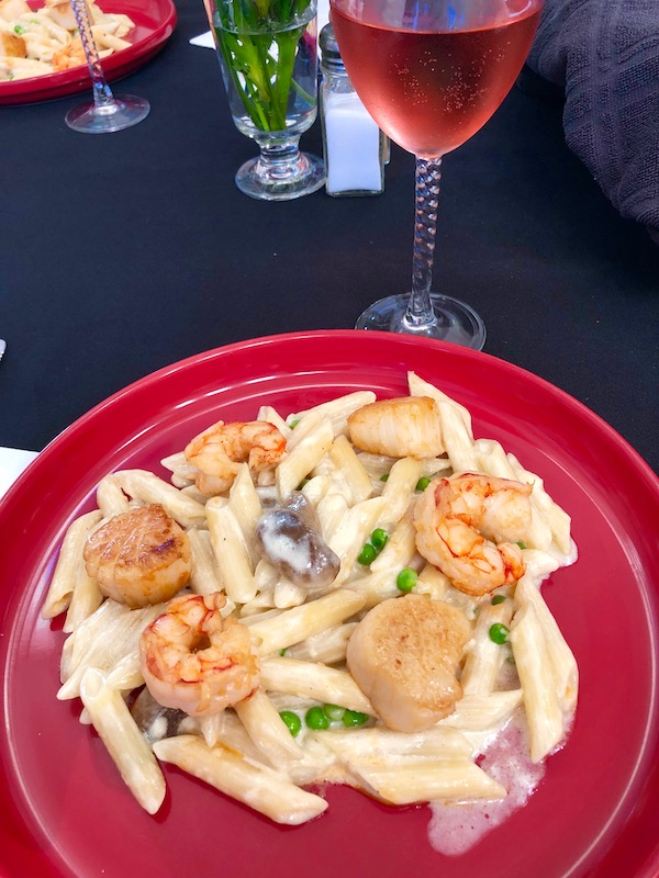 A large red dinner plate topped with pasta, shrimp and scallops in creamy sauce at the Mellon Patch Inn on N. Hutchinson Island Florida.