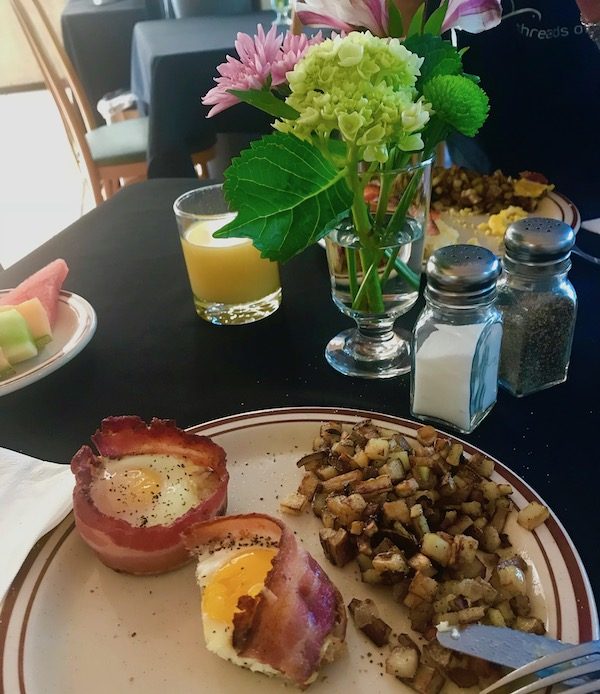 A dining table with black linen set with orange juice, fresh flowers and a plate filled with two baked bacon and egg cups and golden brown hash brown potatoes at the Mellon Patch Inn on N. Hutchinson Island Florida.