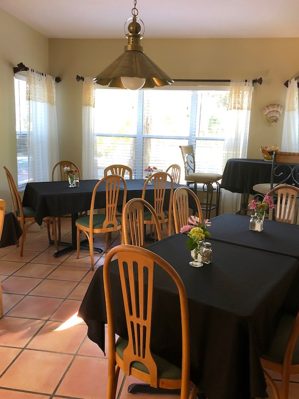 A dining room set with black linen and fresh flowers at Mellon Patch Inn on N. Hutchinson Island Florida.