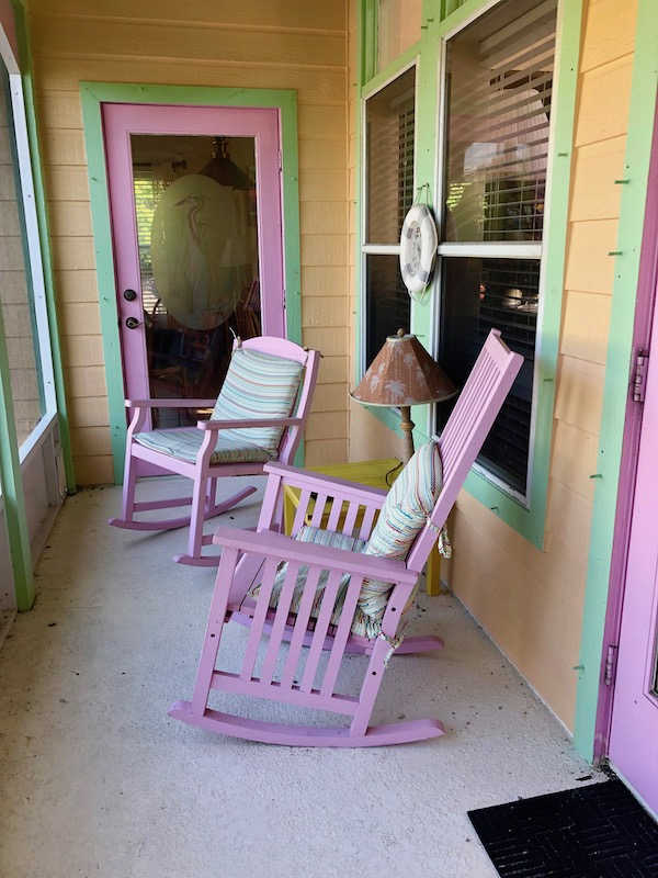 A couple of pink rocking chairs on a porch at Mellon Patch Inn on N. Hutchinson Island Florida.