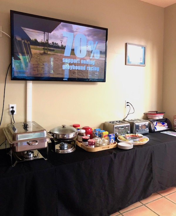 A buffet table with black lined displaying breakfast item with a large flat screen TV above it at the Mellon Patch Inn on N. Hutchinson Island Florida.