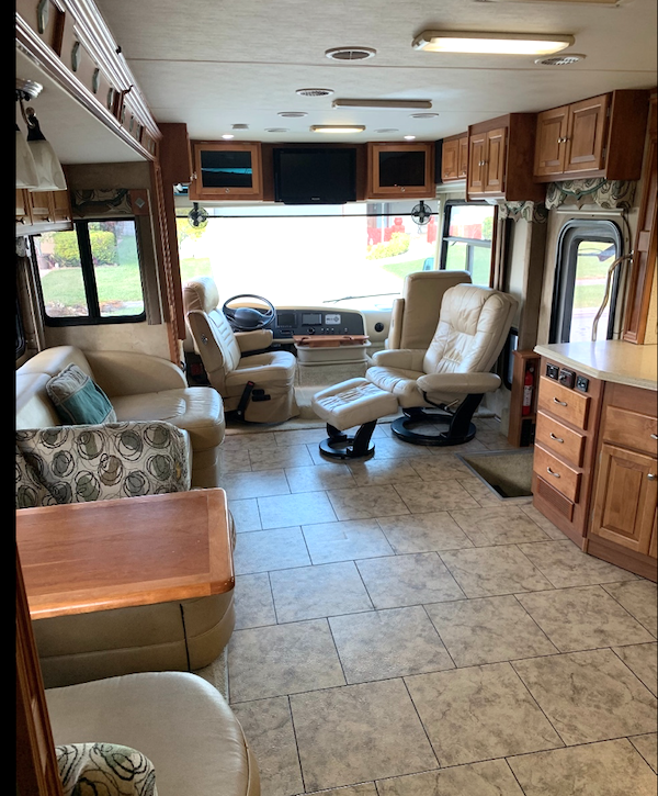 Living room and dining area with rear TV. Linoleum tile on the floor and front TV above windshield.