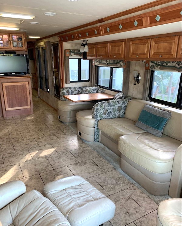 RV Living room and dining area with rear TV. The leather sofa is ivory and the dinette has ivory leather seats with upholstered backs and a wood table