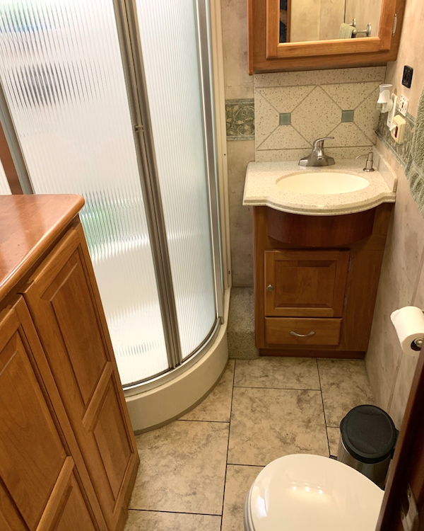 An RV bathroom with rounded from glass shower.