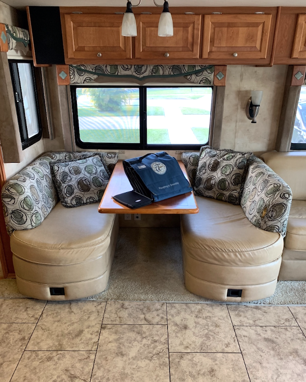 An RV dinette with ivory leather seats and upholstered backs.