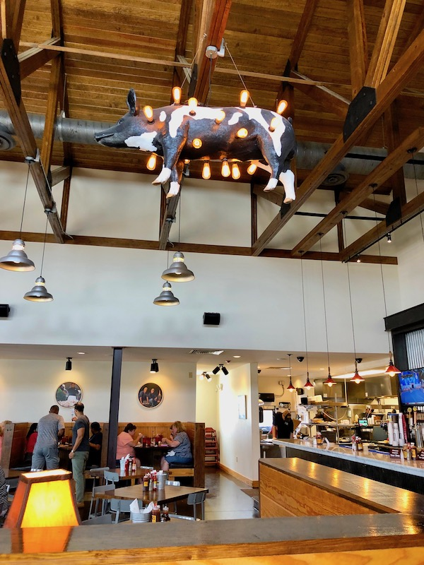 Inside a bbq restaurant with a cow sculpture with lightbulbs hanging from the rafters