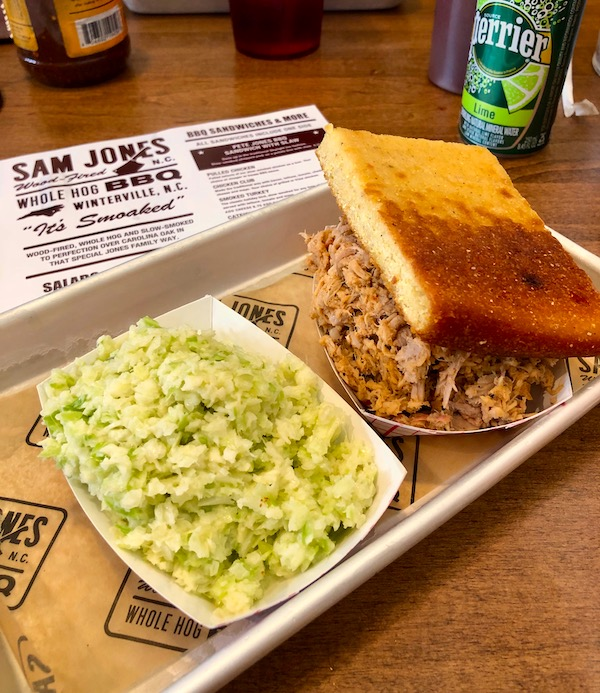 Sitting atop a menu from Sam Jones BBQ is a quarter sheet tray holding chopped pork, a slice of toasted cornbread and a paper container of coleslaw.