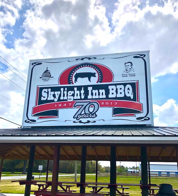 A covered pavilion with a huge sign that reads Skylight Inn BBQ