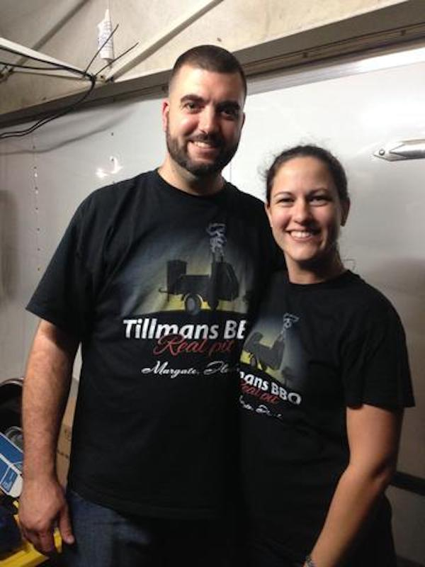 A man and a woman in black t-shirts inside a cooking trailer.