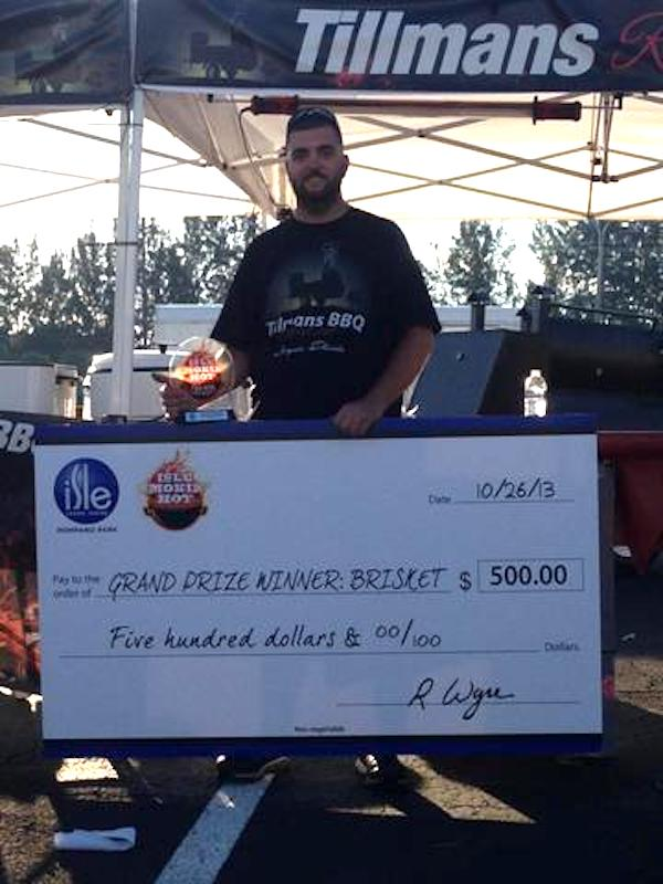 A man in a black t-shirt holding a huge check for $500 for winning the Grand Championship for Brisket.