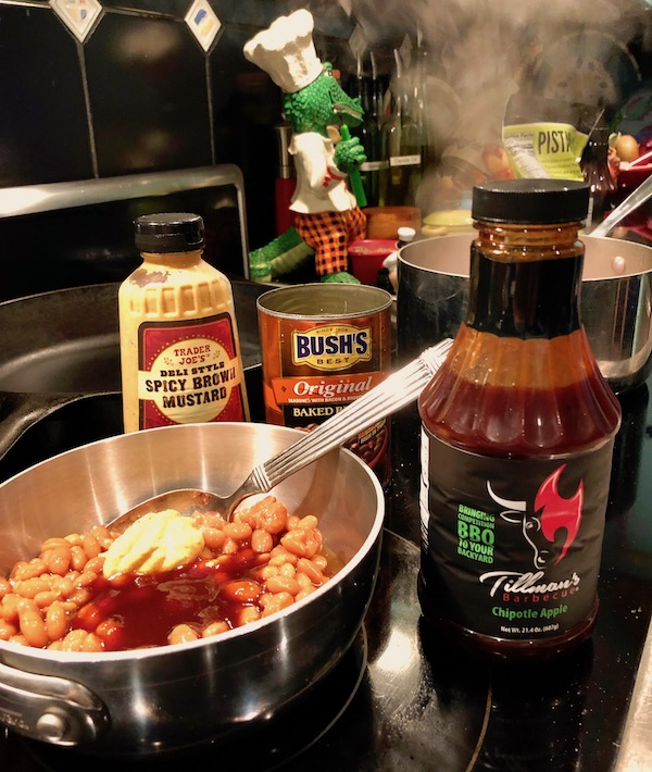 A pot of beans on the stove with mustard and bbq sauce added. Surrounding the pot are a bottle of Tillman's Apple Chipotle BBQ Sauce, an empty can of Bush's Original beans and a bottle of Trader Joe's Spicy Deli Style mustard.