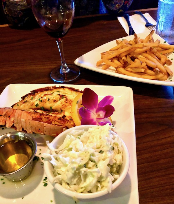 12A Buoy Great Casual Dining in Ft. Pierce Florida entrée of broiled lobster tail on a white square plate with melted butter and coleslaw garnished with a purple orchid. Also a plate of golden French fries.
