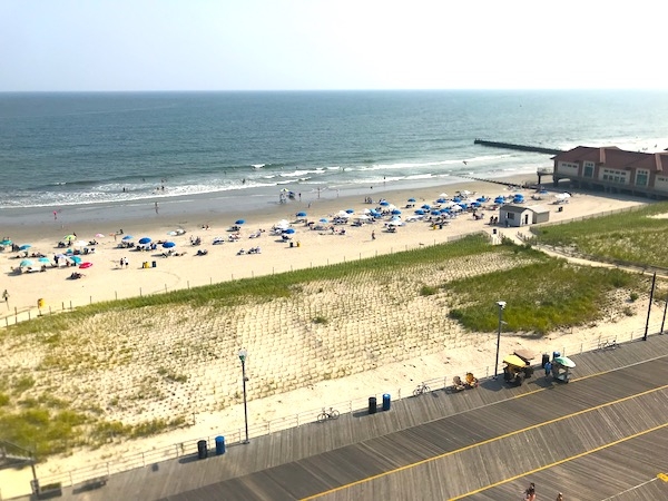 Dunes and white sand beach with blue umbrellas and boardwalk are Fun Things at the Jersey Shore.