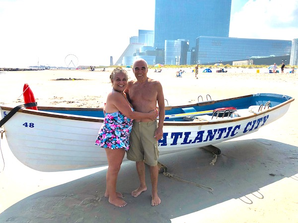 A couple in bathing suits on the beach in front of a row boat that's named Atlantic City enjoying Fun Things at the Jersey Shore.