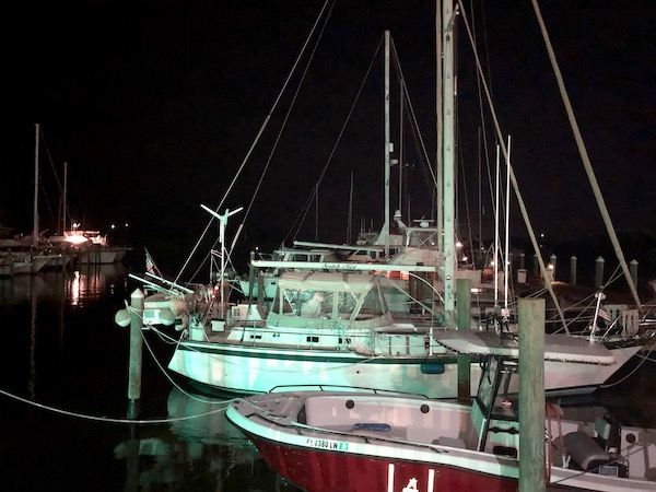 A marina with boats and inky dark water at Harbor Cove Bar and Grill in Ft. Pierce Florida