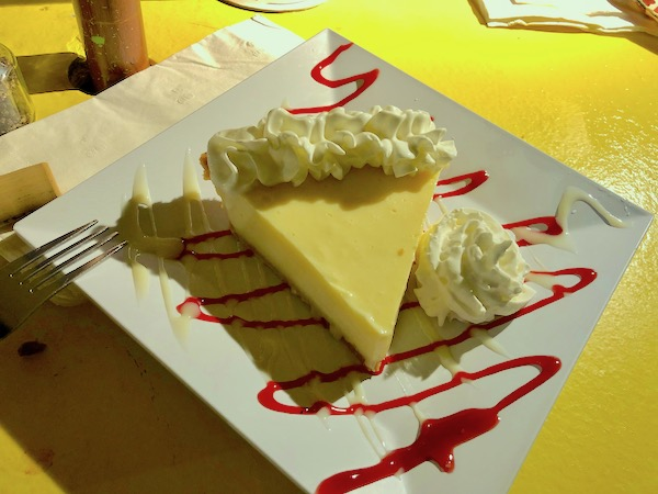 Harbor Cove Bar and Grill in Ft. Pierce Florida a square white plate topped with a slice of key lime pie and drizzled with raspberry coulis.