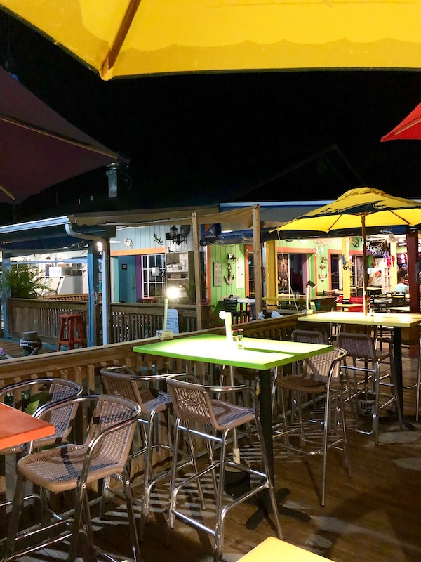 A casual outdoor dining room with colorful market umbrellas and tables at Harbor Cove Bar and Grill in Ft. Pierce Florida.