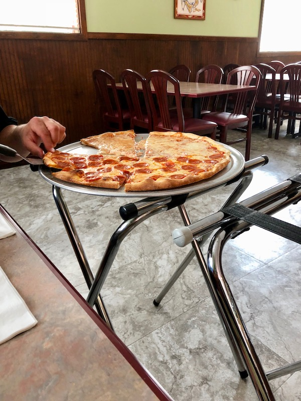 A tray stand topped with a half pepperoni, half cheese pizza at Jo Jo's Pizza Galloway, New Jersey.