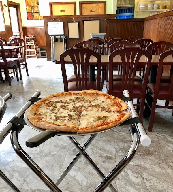 A tray stand topped with a sausage pizza at Jo Jo's Pizza Galloway, New Jersey.