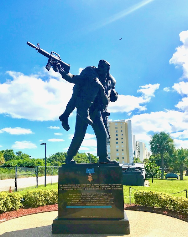 Navy Seal Museum on N. Hutchinson Island Florida Statue of a Navy Seal with a rifle carrying a fallen Navy Seal on his shoulders.