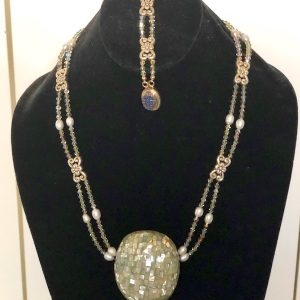 Swarovski Crystal, Pewter and Abalone Necklace and Bracelet on a black velvet display stand.
