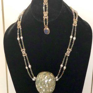 Swarovski Crystal, Pewter and Abalone Necklace and Bracelet on a black velvet display stand.