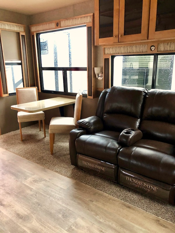 Vilano 5th Wheel by Vanleigh two dark brown leather recliners and a dining table with two chairs by a large window.