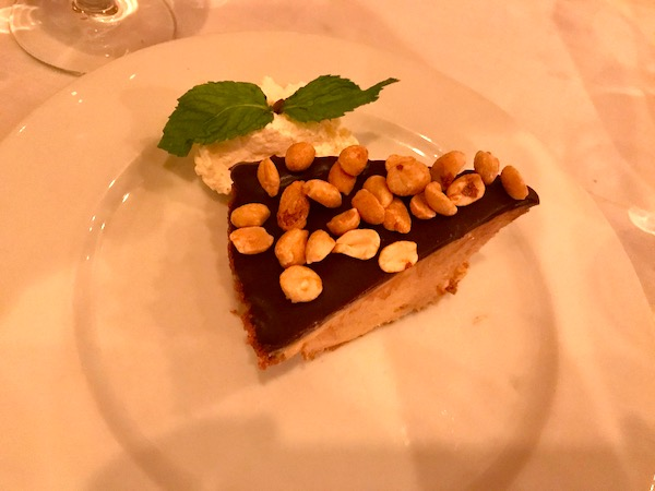 A slice of chocolate peanut butter pie topped with whole peanuts on a white plate at Steve and Cookie's in Margate NJ.