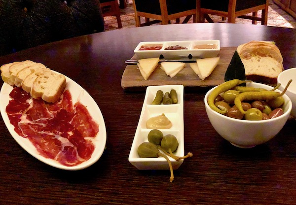 Chef José Garces' Amada Offers Tapas at its Best including this white oval plate of Jamon Iberico with slices of baguette, cheeses with mustards, a trio of condiments and a bowl of assorted olives and pickles.