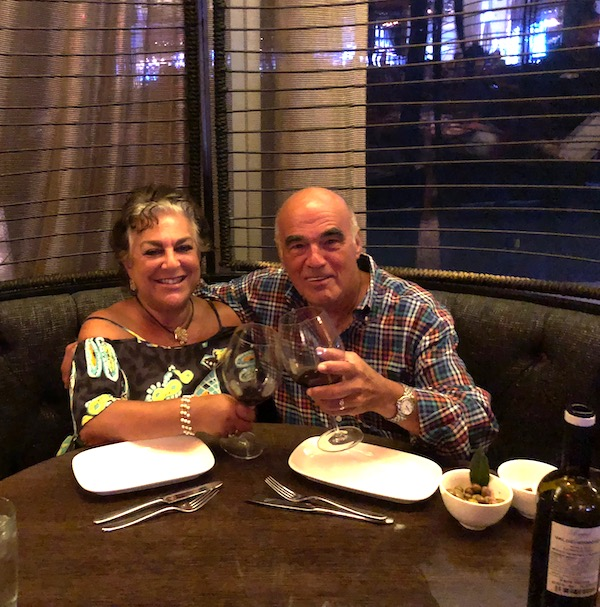 A man and a woman in a booth clinking wine glasses at Chef José Garces' Amada Offers Tapas at its Best.