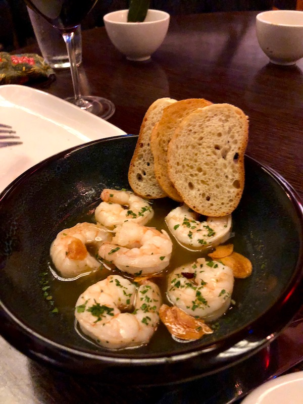 Chef José Garces' Amada Offers Tapas at its Best with this black plate topped with garlic shrimp and crusty bread.