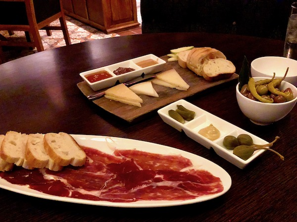 Chef José Garces' Amada Offers Tapas at its Best including this white oval plate of Jamon Iberico with slices of baguette, cheeses with mustards and a trio of condiments.