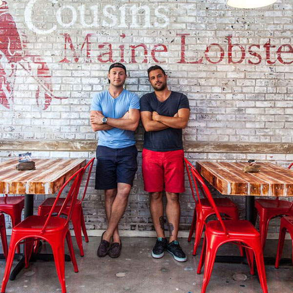 Two young men standing against a white brick wall from Cousins Maine Lobster at the Morgan Street Food Hall.